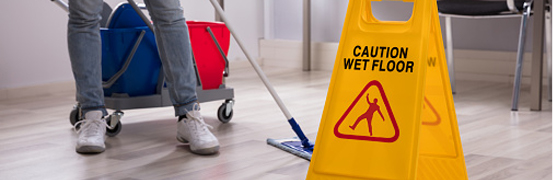 someone cleaning a floor along a wet floor sign