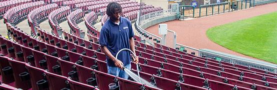 a man power washing baseball stadium
